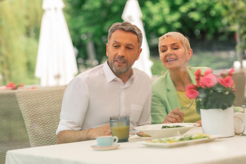 Grey-haired handsome husband having breakfast with beautiful wife stock image