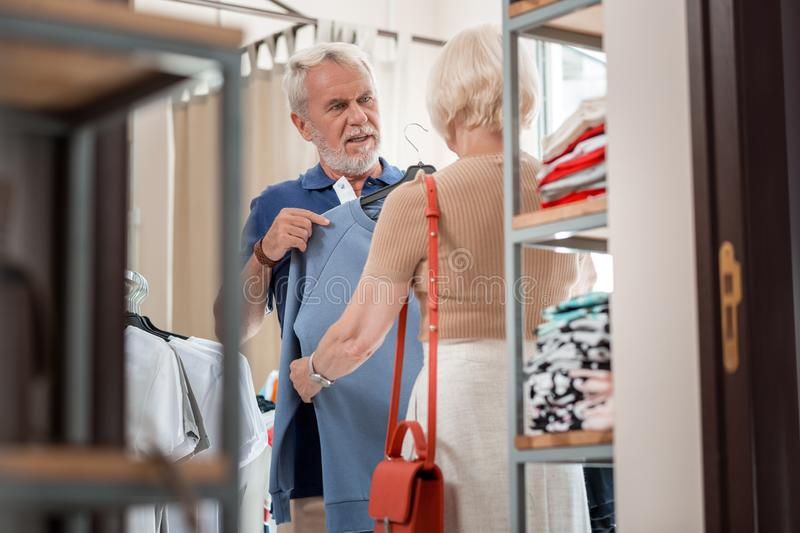 Grey haired husband being in doubt while choosing a pullover with his wife. Hesitation. Waist up of grey haired husband looking at his wife with doubt while stock photos