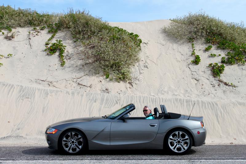 Grey Haired Man in Convertible by Sand Dunes stock photo