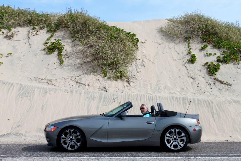 Grey Haired Man en convertible por las dunas de arena foto de archivo
