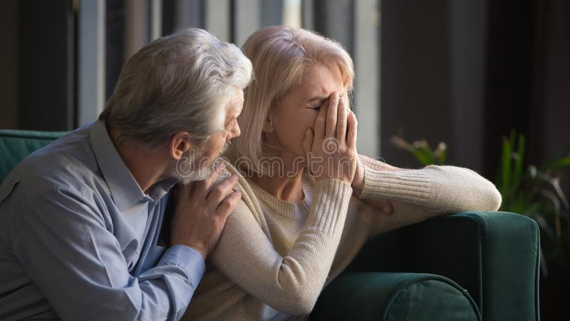 Grey haired man supporting crying unhappy mature woman stock photos