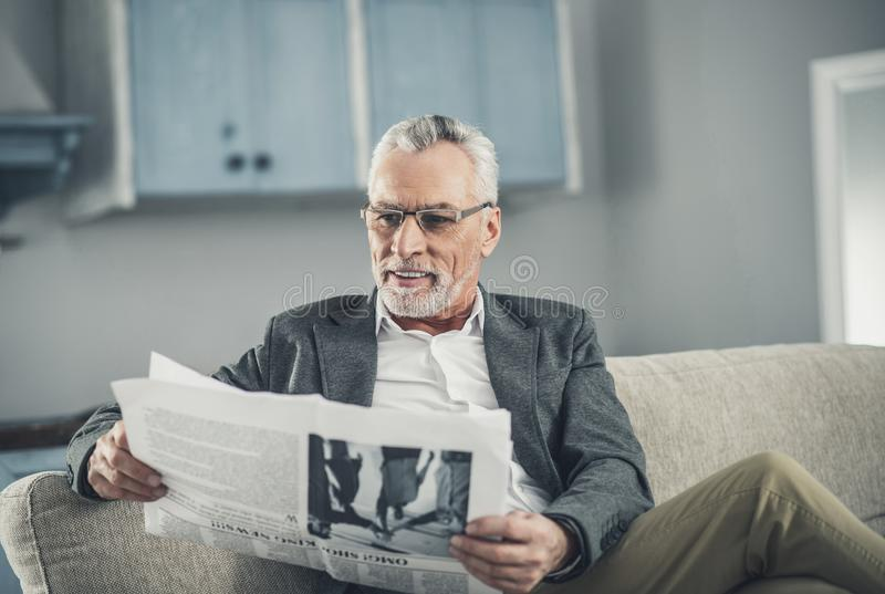 Grey-haired man wearing glasses reading positive news stock image