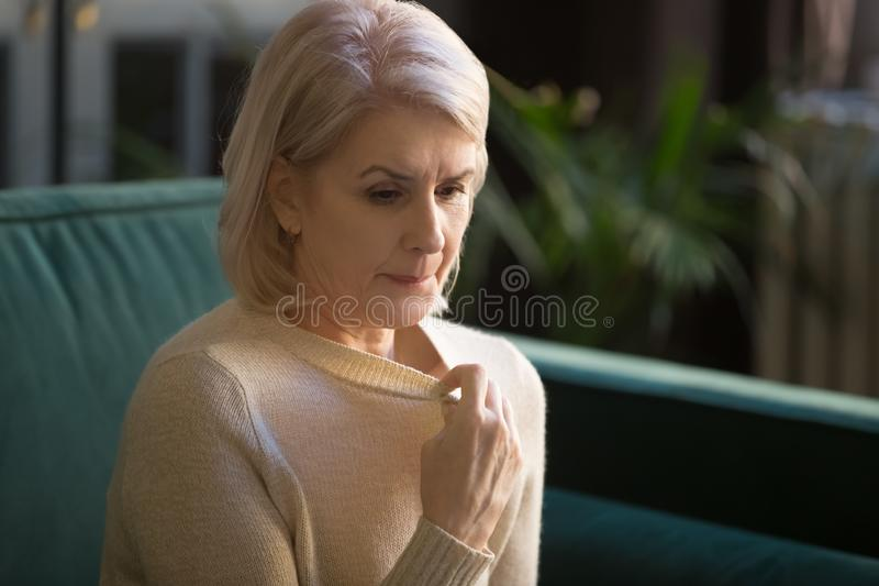 Grey haired mature woman in sweater suffering from high temperature. Grey haired mature woman suffering from heat stroke, blowing under sweater, feeling stock images