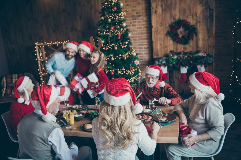 Grey-haired man speak talk with granddaughter sit eat food on table in house with christmas x-mas eve where man in santa. Grey-haired men speak talk with royalty free stock images