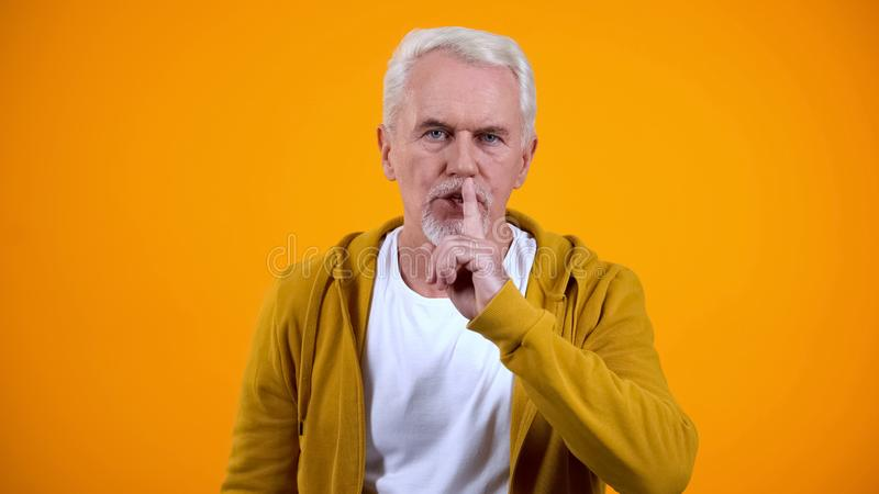 Grey-haired pensioner showing silence gesture against orange background, secret stock images