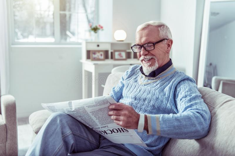 Grey-haired retired man smiling while reading positive local news royalty free stock image