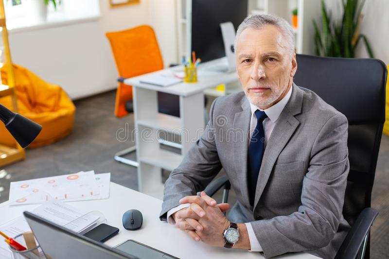 Grey-haired strict man in grey costume being concentrated at work. Dealing with laptop. Grey-haired strict man in grey costume being concentrated at work while royalty free stock image