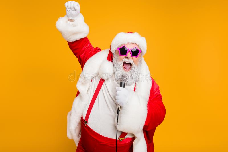 Grey haired stylish christmas grandfather in red hat cap celebrate x-mas party hold microphone sing noel carols feel royalty free stock photos