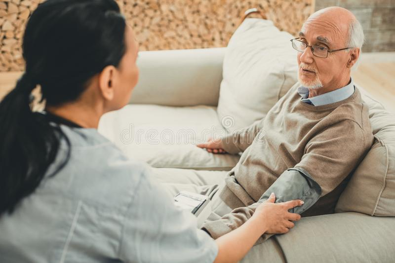 Grey-haired tired man having his blood pressure measured. Reading blood pressure. Grey-haired tired men having his blood pressure measured by medical device with royalty free stock images