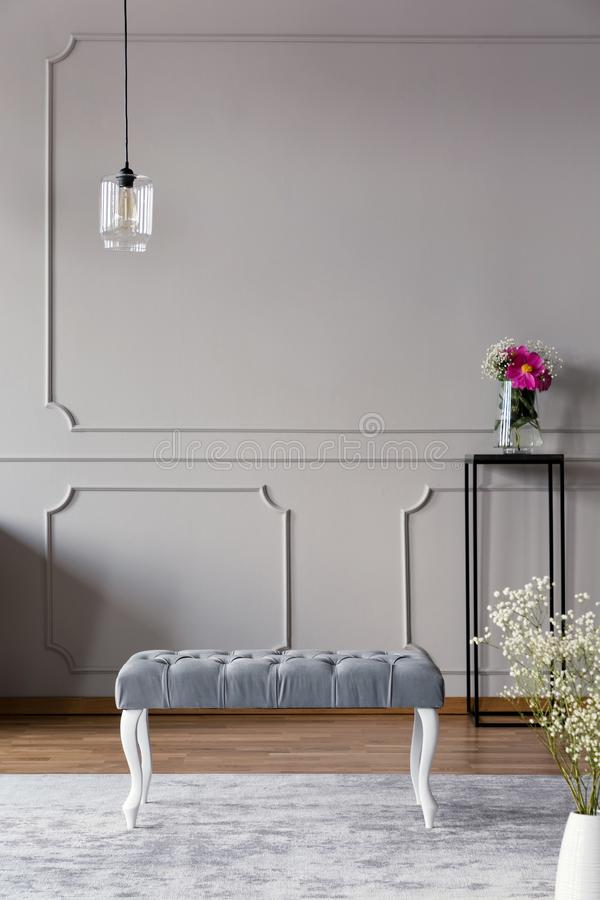 Grey hallway interior with a bench, lamp and flower in a vase on a stand. Real photo. Place for your poster. Grey hallway interior with a bench, lamp and flower royalty free stock photos