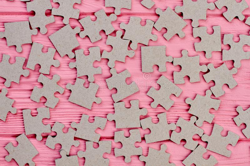 Grey jigsaw puzzles close up. Cardboard puzzles on pink wooden background close up stock photo