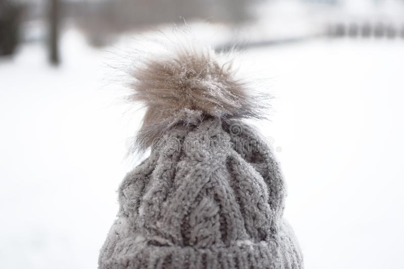 Grey knitted hat with fure pompon royalty free stock photos