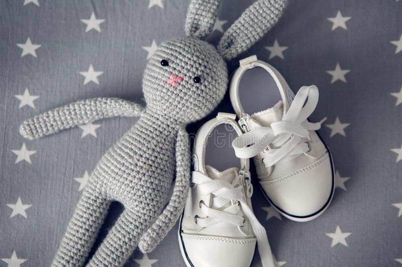 Grey knitted toy rabbit, and children`s white shoes are on grey background. With stars stock photos