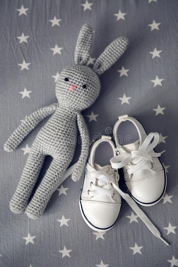 Grey knitted toy rabbit, and children`s white shoes are on grey background stock photos