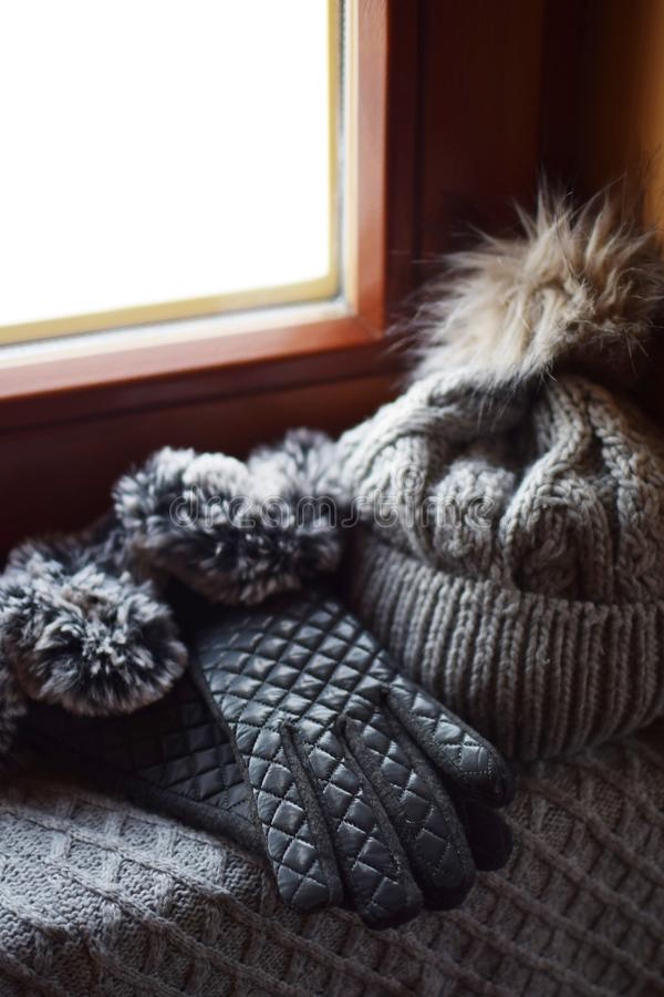 Grey knitted woolen scarf, gloves and hat. With fur pompon on windowsill. Winter still life background with warm accessories at brown wooden window royalty free stock photography