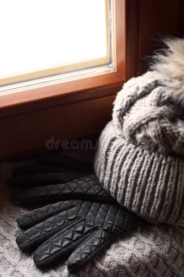 Grey knitted woolen scarf, gloves and hat. With fur pompon on windowsill. Winter still life background with warm accessories at brown wooden window royalty free stock photos
