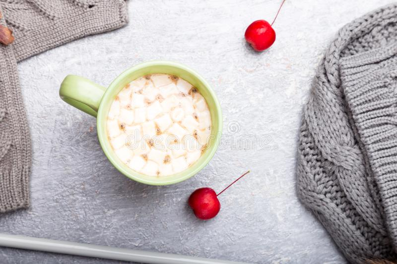 Grey knitting gloves, scarf, hat and needles around cup of coffee with marshmallow on grey background. Top view. Copy space. Knitt. Ing yarn royalty free stock images