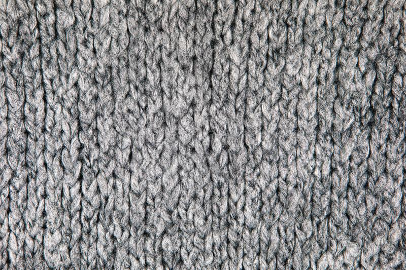 Grey Knitwear Fabric Texture. Loose Knitwear Fabric Texture with wool fibers. Repeating Machine Knitting Texture of warm Sweater. Grey Knitted Background blanket royalty free stock image