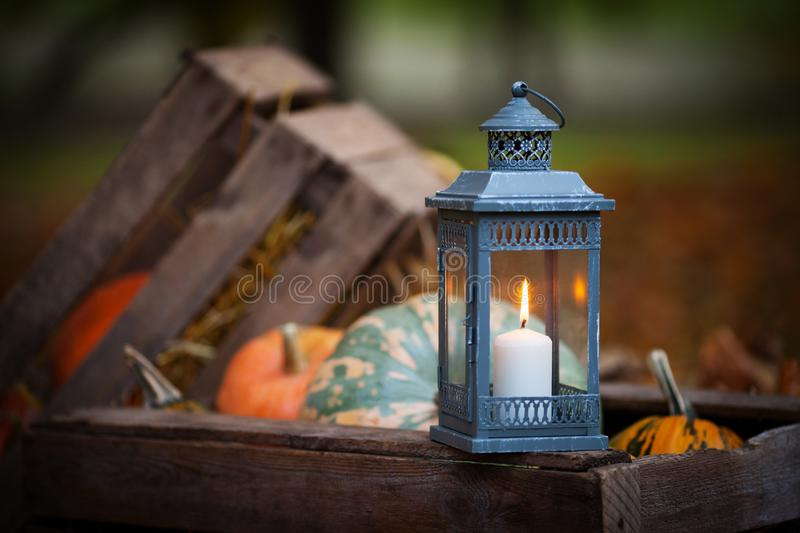 Grey lantern with burning candle on wooden box decorated in autumnal style,   in rustic style. Concept of autumn. Copy space. Grey lantern with burning candle on royalty free stock images
