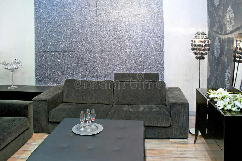 Grey living room. Contemporary sitting area with grey sofa and table royalty free stock image