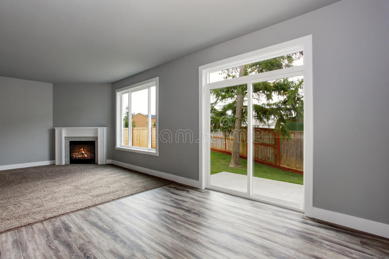 Grey living room interior. Windows and Glass doors overlooking the back yard. stock image