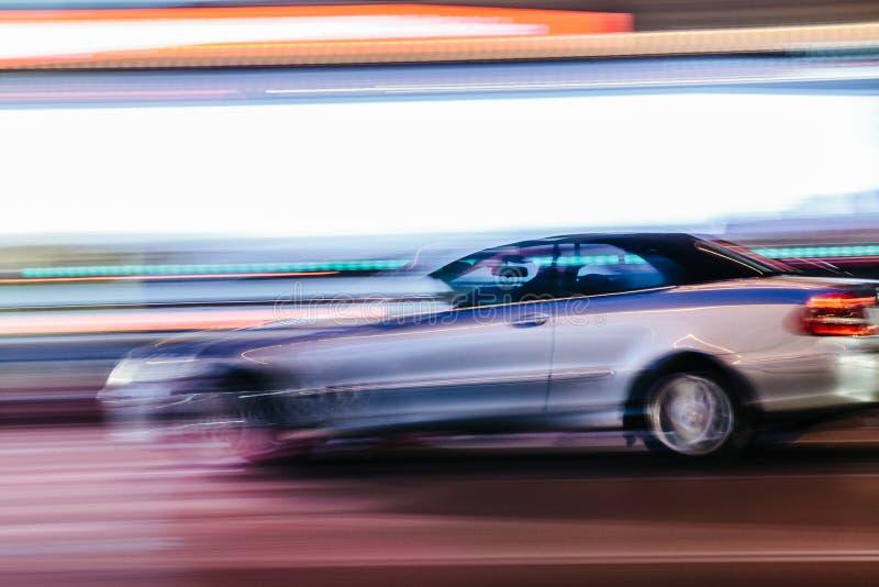 Grey Luxury Car dans une scène brouillée de ville photographie stock libre de droits