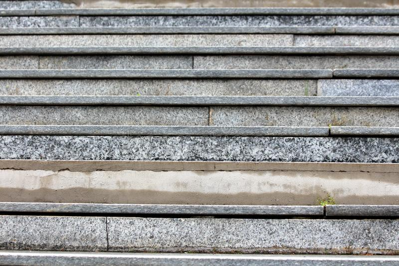 Grey marble tiles staircase texture with fallen cracked tiles and visible concrete foundation royalty free stock photos