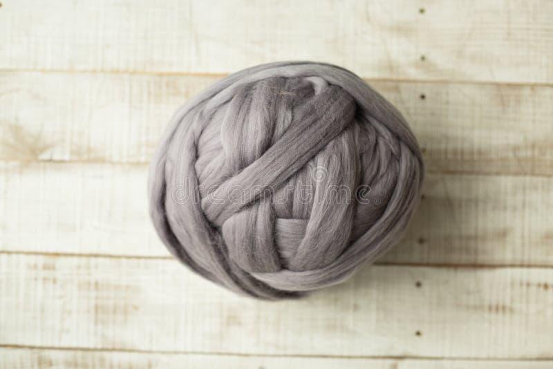 Grey merino wool ball. On wooden background stock image