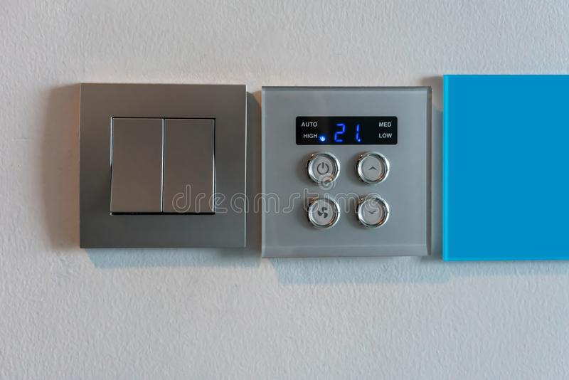 Grey metallic light switch and air condition controller with digital display against white wall stock image