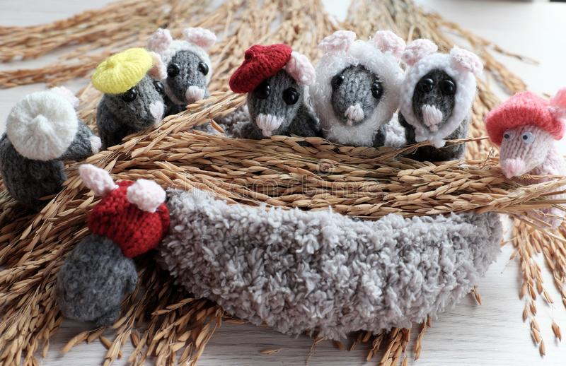 Grey mice, tiny rats with sheaf of yellow paddy. Colorful close up group of grey mice with sheaf of yellow paddy, tiny rats knit from yarn make funny concept stock photography