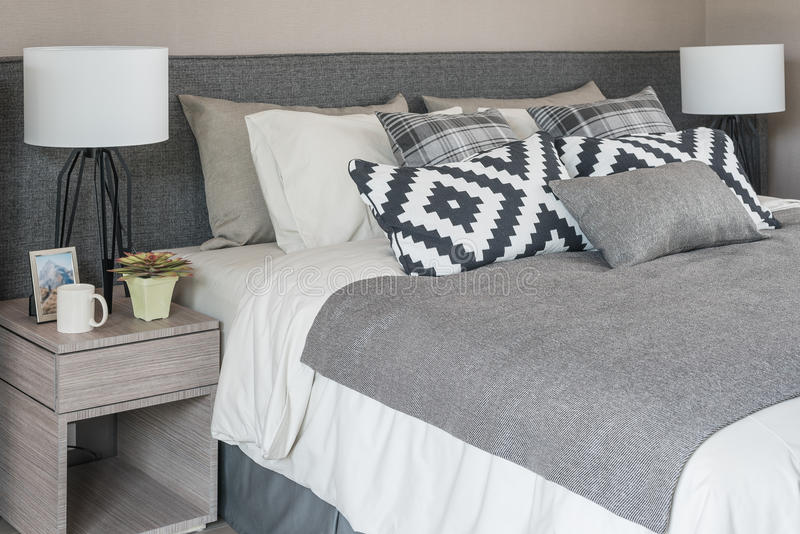 Grey modern bed with black and white pillows stock photography