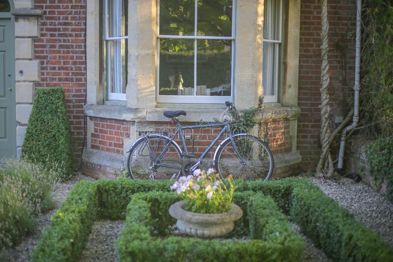 Grey Mountain Bike Leaning on Brown Wall Brick in Garden stock photos