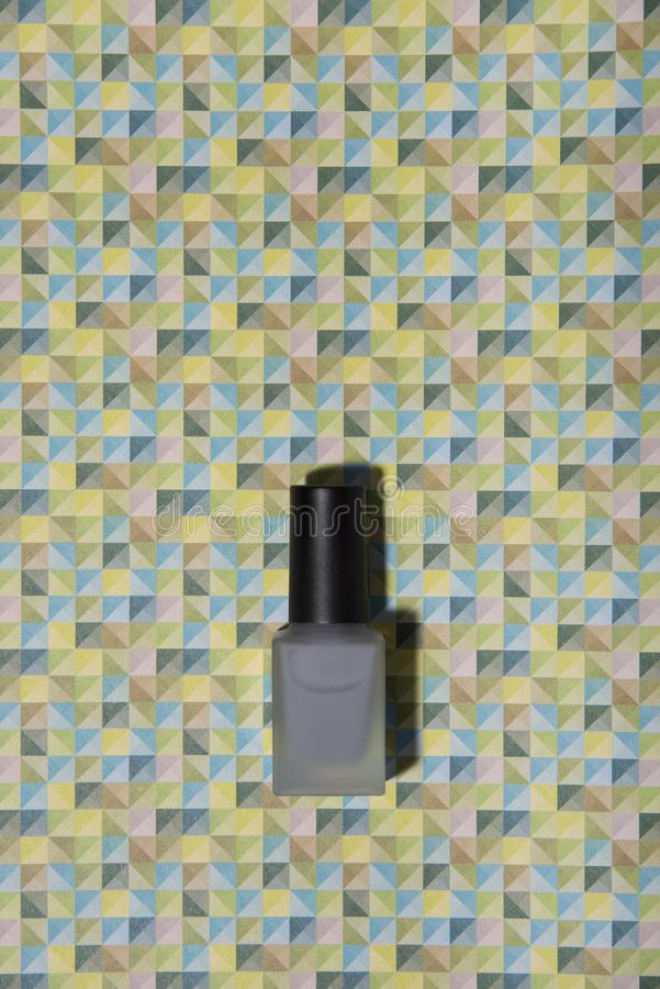 Grey nail lacquer on trendy graphic patterned colorful background. royalty free stock images