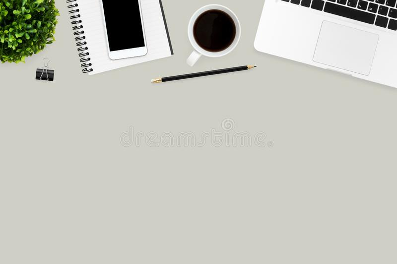 Grey office desk table with laptop computer, cup of coffee, smartphone and supplies. Top view with copy space, flat lay stock images