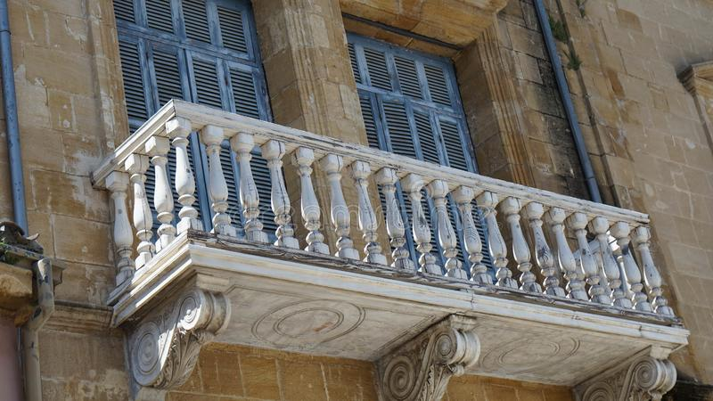 Grey old stone balcony to the yellow brick house in Cyprus stock photo
