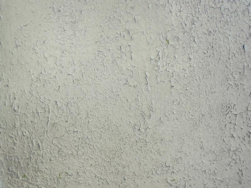 Grey paint peeling on a metallic surface background. Old grungy, weathered painted wall texture. Cracked, dirty, silver plaster royalty free stock photo