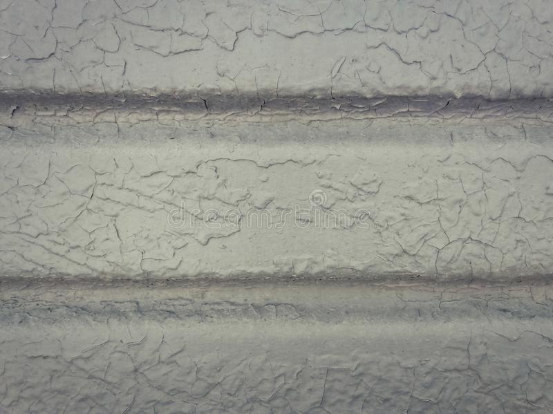 Grey paint peeling off a metallic surface background. Old grungy, weathered painted wall texture. Cracked, dirty, silver plaster. Falling off the construction stock photo