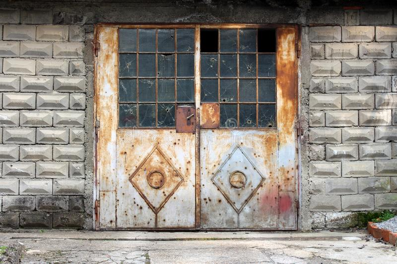 Grey partially rusted metal doors with small door handle and broken safety wire protection glass mounted on concrete wall. With stone tiles with concrete stock images