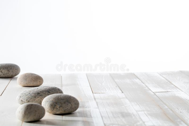 Grey pebbles for meditation, mindfulness, mineral spa or white emptiness. Grey pebbles and stones set on white wooden background for meditation, mindfulness royalty free stock image