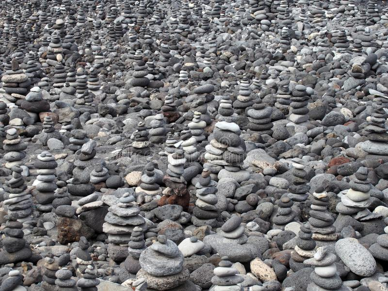 Grey pebbles and stones on a beach arranged into a large collection of piles and towers filling the frame royalty free stock photography