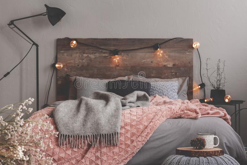 Grey and pastel pink blanket on grey bedding of fashionable bedroom with rustic design. Grey and pink blanket on grey bedding of fashionable bedroom with rustic stock photo