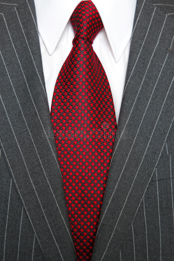 Grey pinstripe suit and red tie. Photo of a grey pinstripe suit with plain white shirt and red patterned tie stock photography