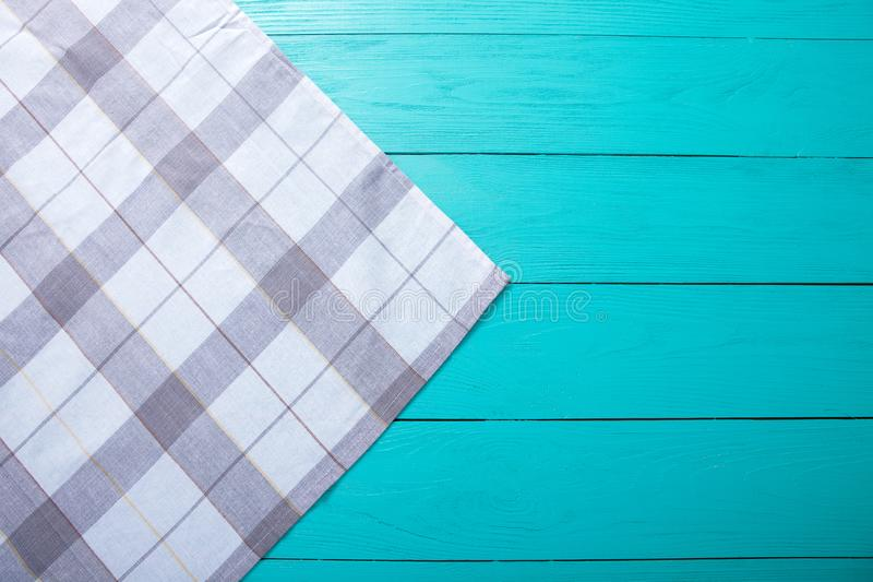 Grey plaid tablecloth on blue rustic wooden table, top view and copy space. Mock up and wood background. royalty free stock photo