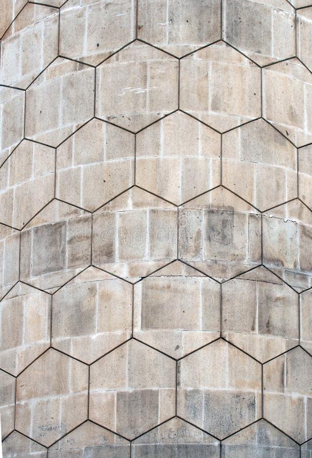 Grey polygon hexagonal pattern on an old curved concrete block exterior wall royalty free stock photo