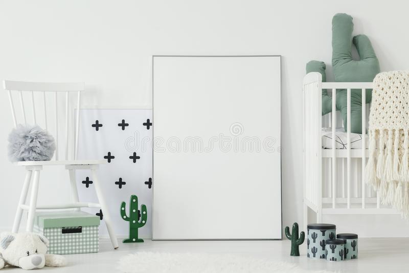 Grey pompom placed on white chair standing in bright baby bedroom interior with cactus shaped decor and empty poster on the floor. Grey pompom placed on white stock images