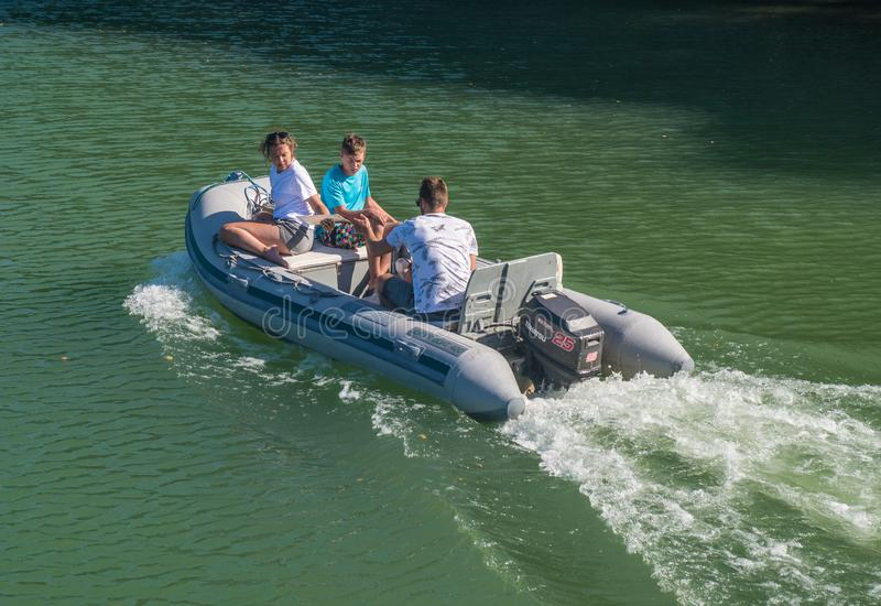 Grey pontoon with outboard engine with people at high speedSmall electric tourist boats for rent mooring. Bigger grey pontoon with outboard engine with three stock images