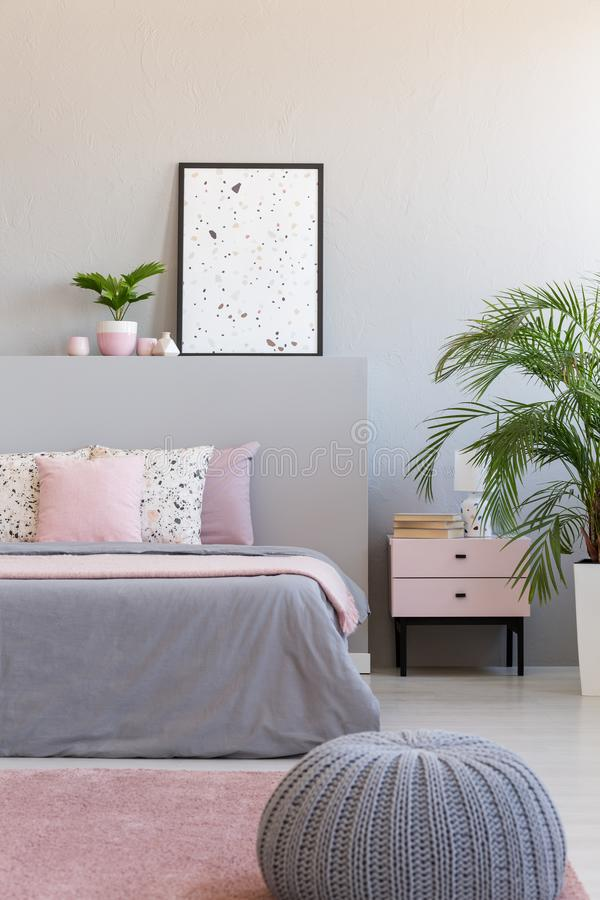Grey pouf next to bed with cushions in modern bedroom interior with poster and plants. Real photo stock images