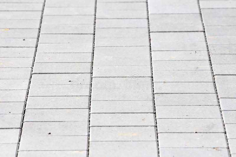 Grey rectangle stone tiles texture at local public park sidewalk on warm sunny summer day. Wallpaper background royalty free stock image
