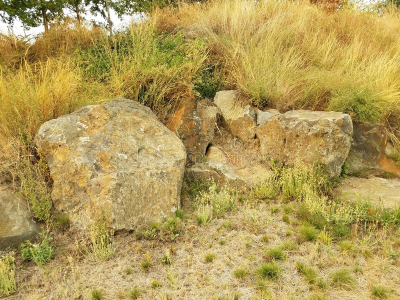 Grey rocks or boulders and green and yellow grasses. Large grey rocks or boulders and green and yellow grasses royalty free stock photo