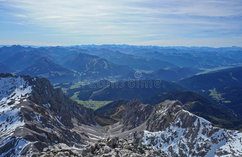 Grey rocks with snow places, village below, mountains and cloudy sky in the background stock image